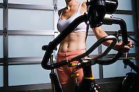 Woman standing near a stationary bicycle in a health club.