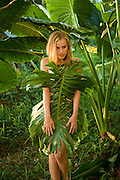 Woman behind tropical leaves, Taveuni, Fiji