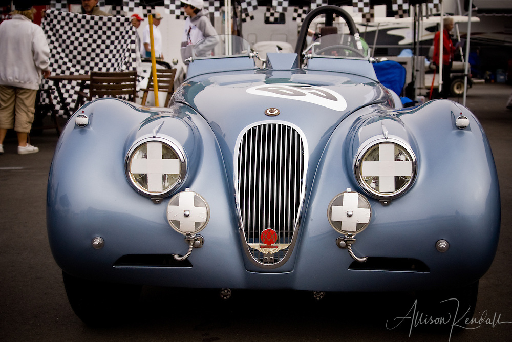 A blue vintage Jaguar sits in the paddock at Laguna Seca between race sessions, during Monterey Car Week
