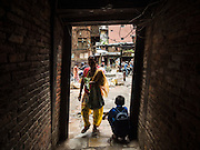 01 AUGUST 2015 - KATHMANDU, NEPAL: A woman walks into a residential courtyard in Kathmandu. Many homes are accessible only through brick tunnels, some of which collapsed in the earthquake. The Nepal Earthquake on April 25, 2015, (also known as the Gorkha earthquake) killed more than 9,000 people and injured more than 23,000. It had a magnitude of 7.8. The epicenter was east of the district of Lamjung, and its hypocenter was at a depth of approximately 15 km (9.3 mi). It was the worst natural disaster to strike Nepal since the 1934 Nepal–Bihar earthquake. The earthquake triggered an avalanche on Mount Everest, killing at least 19. The earthquake also set off an avalanche in the Langtang valley, where 250 people were reported missing. Hundreds of thousands of people were made homeless with entire villages flattened across many districts of the country. Centuries-old buildings were destroyed at UNESCO World Heritage sites in the Kathmandu Valley, including some at the Kathmandu Durbar Square, the Patan Durbar Squar, the Bhaktapur Durbar Square, the Changu Narayan Temple and the Swayambhunath Stupa. Geophysicists and other experts had warned for decades that Nepal was vulnerable to a deadly earthquake, particularly because of its geology, urbanization, and architecture.          PHOTO BY JACK KURTZ