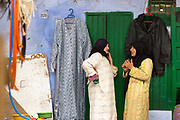 TETOUAN, MOROCCO - 5th April 2016 - Two women talking and gossiping while standing besides clothing items for sale in the Tetouan Medina, Rif region of Northern Morocco.