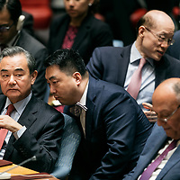 Chinese Foreign Minister Wang Yi speaks with aids before a Security Council meeting on nuclear non-proliferation during the 72nd UNGA.
