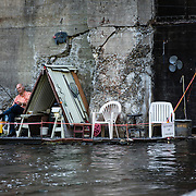 A fisherman sits quietly across a wildwater competition.