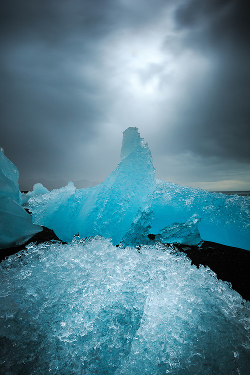 A bright opening in a storm cloud highlights the unique shape, texture, and colors of the icebergs found on the black sand shores of the Jökulsárlón lagoon in Skaftafell National Park.