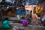 Under the supervision of their parents, Jyoti, 13, (left) her sisters Arti, 18, (back) and Poonam, 12, (front) are making Rangolis, Hindu floor decorations, ahead of celebrations for Diwali, the festival of lights, while in front of their newly built home in Oriya Basti, one of the water-contaminated colonies in Bhopal, central India, near the abandoned Union Carbide (now DOW Chemical) industrial complex, site of the infamous '1984 Gas Disaster'. A Rangoli, also known as Kolam or Muggu is folk art from India in which patterns are created on the floor, in living rooms or courtyards, using materials such as rice, dry flour, coloured powders and flower petals.