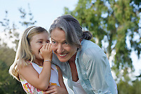 Young blonde girl whispering in grandmother's ear