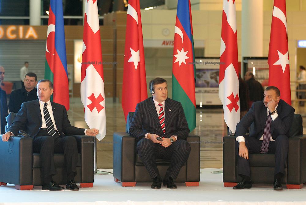 Mit einer offiziellen Feierlichkeit wurde in Tiflis der neue internationale Flughafen eröffnet. Zahlreiche Gäste aus dem In- und Ausland nahmen teil als georgiens Präsident Saakaschwili (mi.) zusammen mit dem türkischen Ministerpräsidenten Edogan (li.) sowie dem aserbaidschanischen Präsidenten Alijew (re.) das rote Band durchschnitten. Der neue Flughafen wurde für rund 90 Mio. Dollar von der türkischen Flughafen-Holding Tepe-Akfen-Vie (TAV) gebaut. (Azerbaijani (ri.), Georgian (mi.) and Turkish (le.) leaders inaugurated a new terminal of the Tbilisi International Airport, which was constructed by the Turkish consortium TAV-Urban, on February 7.)