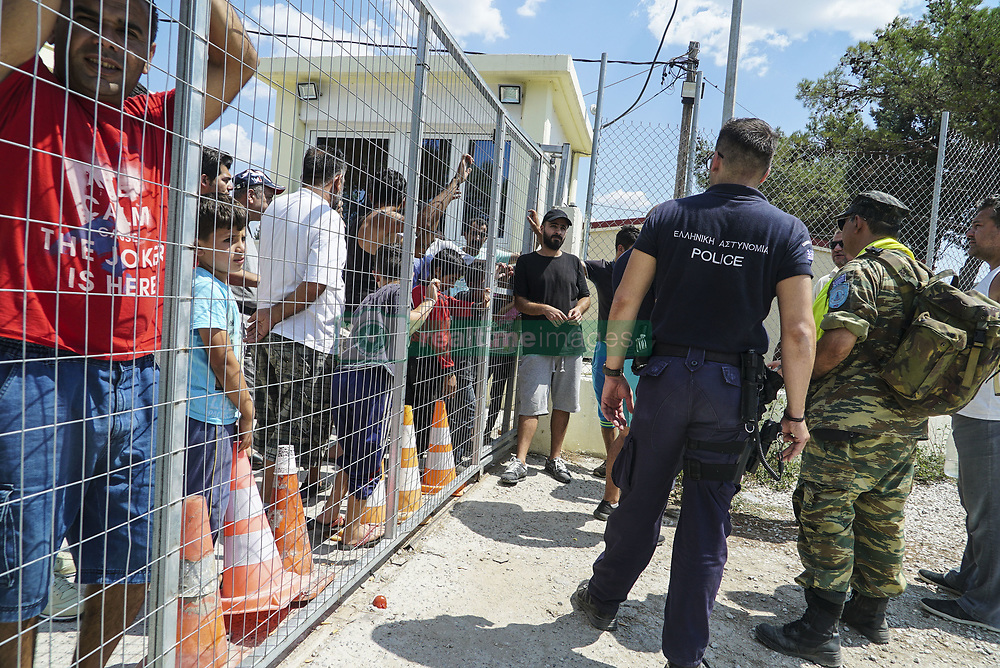August 17, 2017 - Thessaloniki, Greece - Refugees are protesting in Diavata Camp (Former Anagnostopoulou military camp), in Thessaloniki, Greece, on August 17, 2017. They blocked the entrance and rushed out all the government and  ngo employees including army and police. Refugees and migrants are from Syria, Iran, Afghanistan, Pakistan and Kurdish in this camp. They are protesting because in the transformed house containers that they live, more people will come. The camp hosts about 350 people with AC, kitchen, WC in each container and the number of the guests can be expanded at least for more 20%. The government is bringing , actually relocation from camps in bad conditions from the islands, 27 people by bus to this camp. Each container house can host 6 people. For the moment in most of the houses live 4 people. Refugees even denied to reunite their families that hold two containers. The ministry arranged a few empty containers but refugees and migrants still keep protesting. Other demands from the refugees are to leave the camp and live in house, relocate to European countries like Germany and organize a school in the camp for little children. Local authorities and police are blocked outside of the camp. The temperature in the camp is about  36°C right now and they still stay outside. (Credit Image: © Nicolas Economou/NurPhoto via ZUMA Press)
