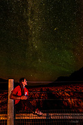 A girl sits atop a fence contemplating the Andromeda galaxy and a faint display of the Northern Lights (aurora borealis) while bathed by the warm light of a nearby cabin at Kestrel Ranch outside Cody Wyoming.  The Andromeda galaxy is visible as the tilted disk of stars to the upper right of the photograph.  Also known as Messier 31, M31, or NGC 224, it is a spiral galaxy approximately 780 kiloparsecs (2.5 million light-years) from Earth. It is the nearest major galaxy to the Milky Way.   Andromeda is approximately 220,000 light years across, and it is the largest galaxy of the Local Group, which also contains the Milky Way, the Triangulum Galaxy, and other smaller galaxies. Andromeda contains one trillion stars, at least twice the number of stars in the Milky Way.  <br /> <br /> (single image)