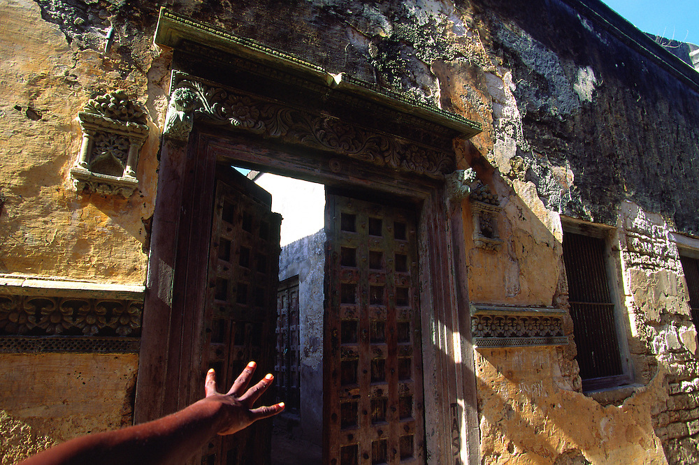 A hand points a house with hindu door in a street in the Stone City in Ilha de Mozambique