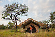 A man stands in front of a safari tent in the morning, holding a cup of coffee while looking over the landscape in the Serengeti National Park. The Serengeti is a UNESCO World Heritage Site.<br /> http://www.gettyimages.com/detail/photo/man-in-front-of-safari-tent-serengeti-royalty-free-image/184058634
