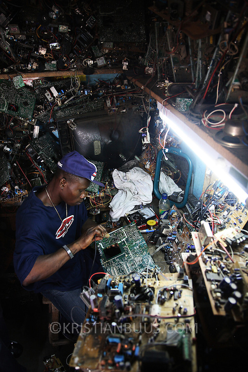 Julius Paul, a TV repair man at Alaba Market.  His speciality is Sharp televisons. Alaba International Market, one of the largest markets for electronic goods in West Africa.  New and old - and a lot of non-working electronic goods such as TVs and computers come in to the market via Lagos harbour from the US, Western Europe and China.