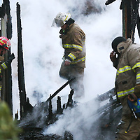 Lauren Wood | Buy at photos.djournal.com<br /> Firefighters with the Palmetto Fire Department walk through the remains of an abandoned home that caught fire Tuesday evening on County Road 900.