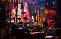 A woman prays and makes offerings of incense at Tin Hau Temple, Hong Kong