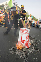 "BANGKOK, THAILAND  -  March 14: Protesters burn placecards as tens of tousands of demonstrators seeking the resignation of Prime Minister Thaksin Shinawatra marched to government house on March 14, 2006 in Bangkok, Thailand. Marching several kilometers from the Grand Palace to Government House the protesters surrounded Thaksin's office chanting ""Thaksin Get Out"", as the Prime Minister threatened a state of emergency if the demonstration turned violent.  (Photo by David Paul Morris)"