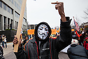 A protestor, wearing a Guy Fawkes mask, 'flips off' policemen observing the Clayton, Missouri march from the top of the Justice Department building.