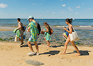 Sands Point, New York, U.S. - July 5, 2014 -  Four friends are walking along sandy shoreline of Sands Point Preserve, including a young woman with an American Flag temporary tattoo on her upper arm, during Independence Day holiday weekend, on the Long Island Sound Gold Coast. The public beach had many visitors this Saturday of the long holiday weekend when sunny warm weather arrived after the rainy July 4th.