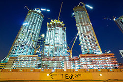 Night view of construction site of new high-rise luxury apartment towers in Dubai United Arab Emirates