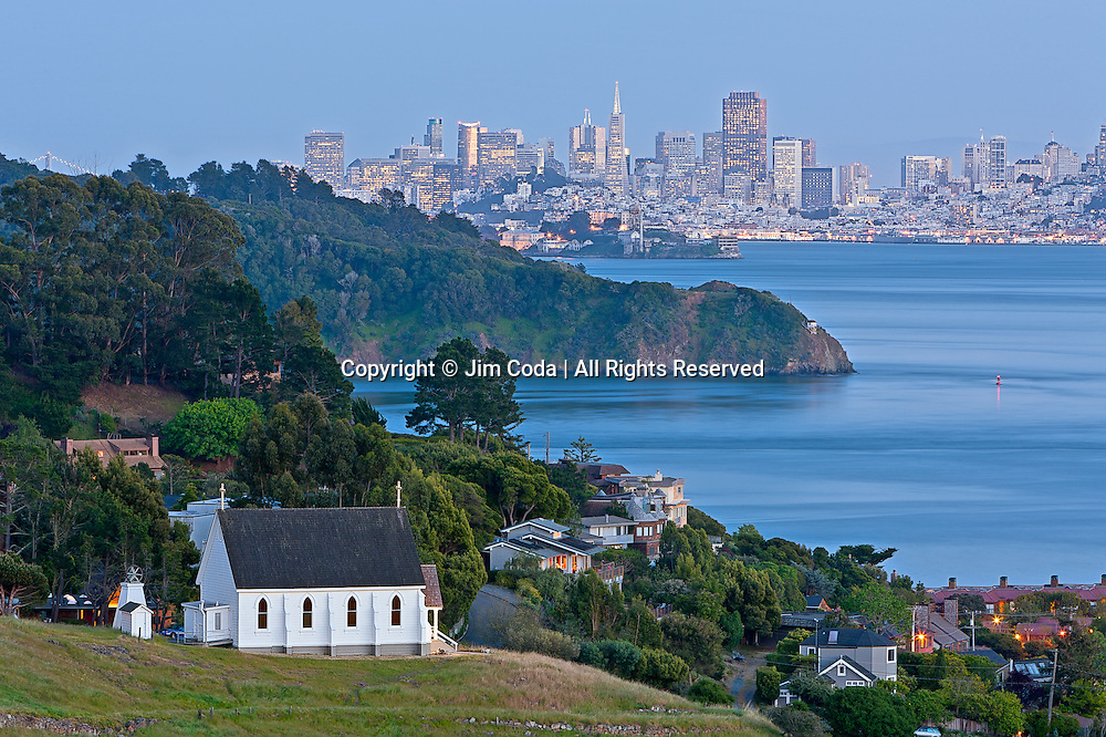 Old St. Hilary's Church at dusk with Angel Island, Alcatraz, and San Francisco in the background.