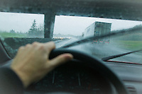 A first person / drivers perspective of driving in an automobile next to a truck trailer on a rainy day while passing below a overpass.