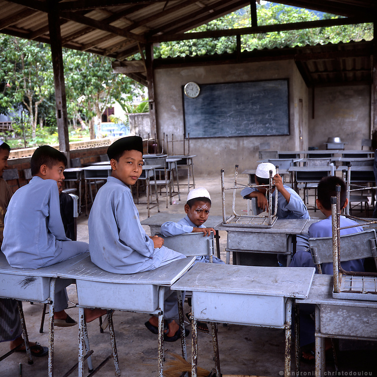 Students at the Mushlim school of the 300-Year Mosque..300-Years Mosque or Wadi Al-Husein Mosque is located at Ban Talomano, Tambon Lubosawo, 25 kms. north of Narathiwat or 4 kms. from Amphoe Bacho on Highway No. 42. As the sign outside it says, it was build in 1624 by Wan Husein, a pioneer of Due Lok Mano Village and an islamic teacher at Sano Village. The whole wood building is a combination of Javanese and local styles of art before the Arab influence.