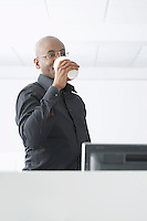 Office worker drinking coffee in office
