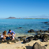 Mom and dad helping their infant son walk along black rocks on Kailua beach, Windward O,ahu