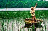Neolithic re-enactment. Stone Age man with antler horn tipped fish spear in animal hide coracle on lake. Kilmartin, Scotland
