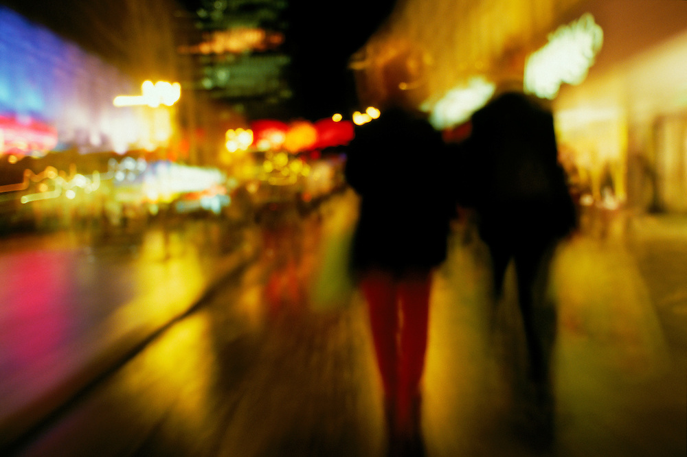Action, blurry, in-motion view of two people walking through a brightly lit city street in Glasgow.