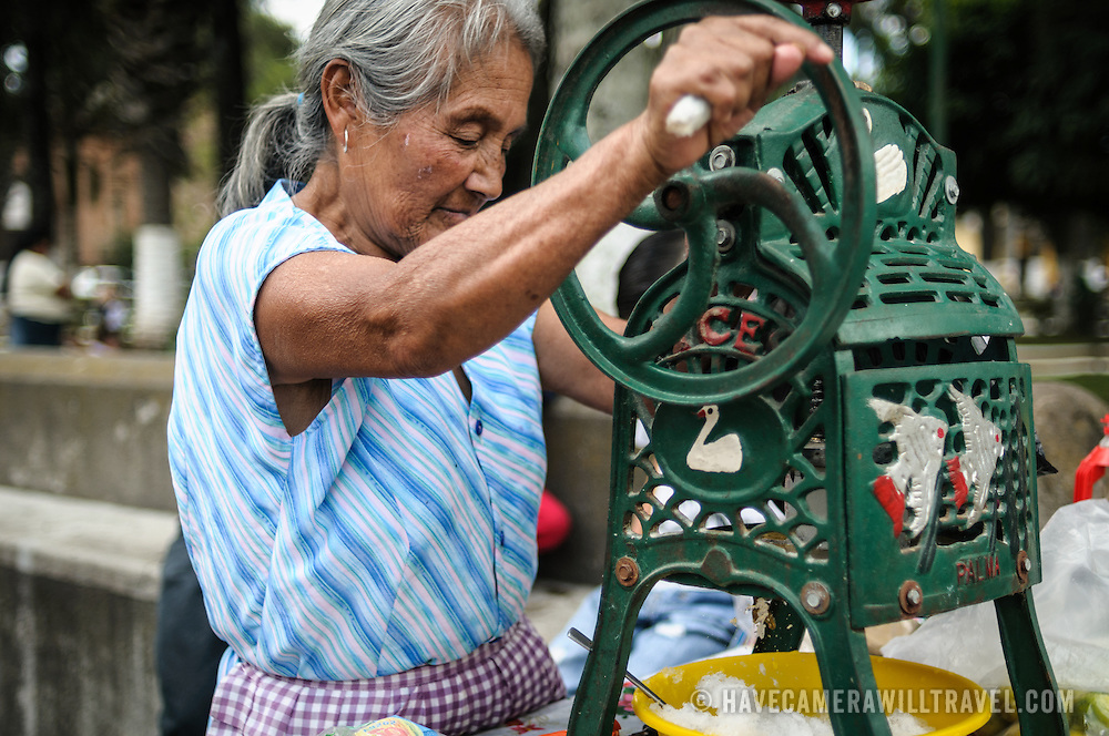 A woman makes shaved ice on a hot day in Guatemala using an old-fashioned mechanical hand crank machine.