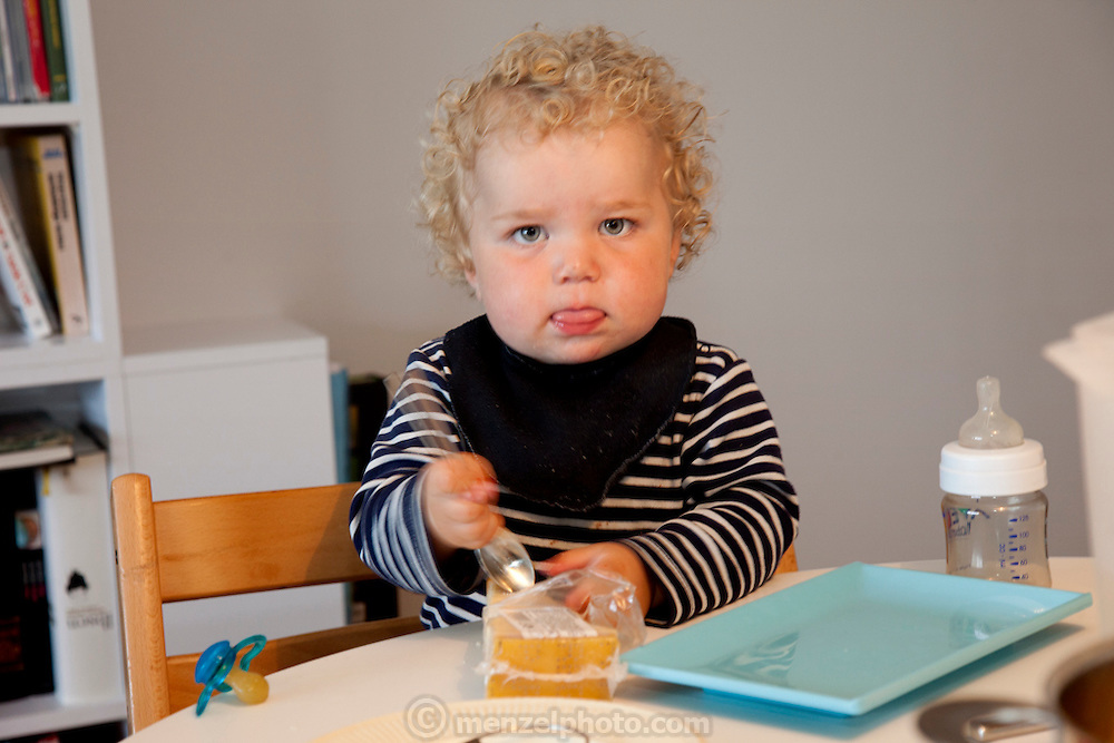Ottersland-Dahl family, of Gjettum, Norway (outside Oslo). Sverre, 1.5, with cheese for spaghetti dinner. Model-Released.