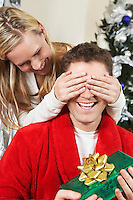 Woman covering eyes of man holding present by Christmas tree