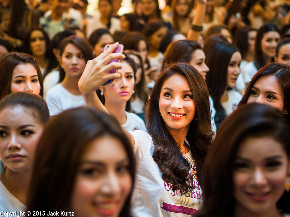 """25 MARCH 2015 - BANGKOK, THAILAND: A contestant uses her smart phone to take a """"selfie"""" before she goes on stage during the first round of the Miss Tiffany's contest at CentralWorld, a large shopping mall in Bangkok. Miss Tiffany's Universe is a beauty contest for transgender contestants; all of the contestants were born biologically male. The final round will be held on May 8 in the beach resort of Pattaya. The final round is televised of the  Miss Tiffany's Universe contest is broadcast live on Thai television with an average of 15 million viewers.     PHOTO BY JACK KURTZ"""