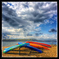 Huntington, NY: October 21, 2014--- Colorful kayaks nestled together on West Neck Beach in Lloyd Harbor with spectacular puffy clouds above them. © Audrey C. Tiernan