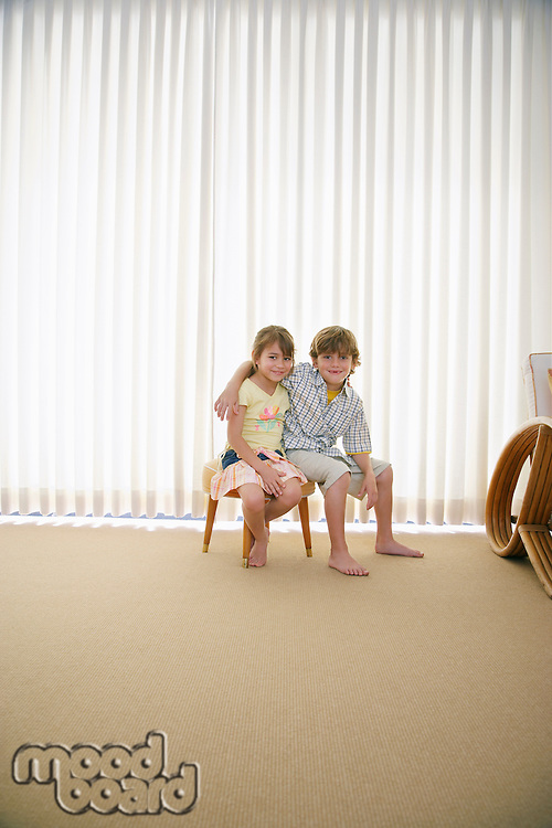 Boy (7-9) and girl (5-6) sitting on stool in room