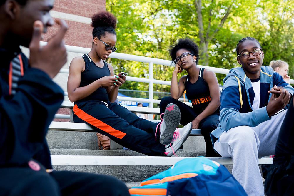Alexis Lowe hangs out with teammates and friend Ashely King, a junior at City High Middle School, during a track meet Tuesday, May 24, 2016, at Comstock Park High School in Comstock Park, Mich. Lowe and King run for Ottawa Hills High School because City High doesn't have enough students for their own team.