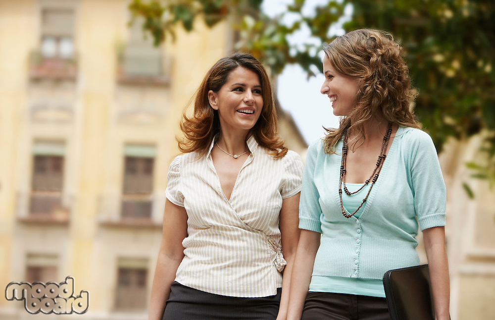 Two businesswomen walking together through old town.