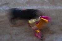 ca. April 1999, Arles, France --- Bull Charging Matador's Cape --- Image by © Owen Franken/CORBIS