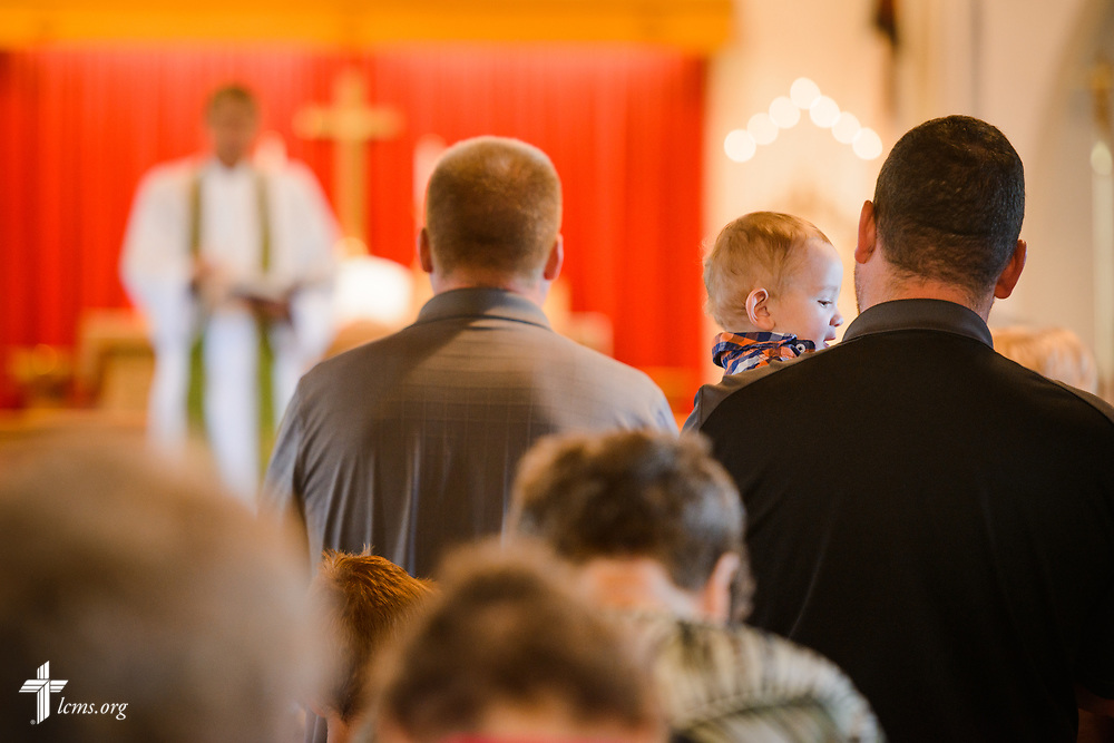 Drew Woods is held while the Rev. Steven Struecker, full-time farmer and pastor of Immanuel Lutheran Church, Livermore, Iowa, and Zion Evangelical Lutheran Church, Lu Verne, Iowa, leads worship at the church in Livermore on Sunday, July 9, 2017. LCMS Communications/Erik M. Lunsford