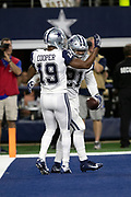 Dallas Cowboys running back Ezekiel Elliott (21) celebrates with Dallas Cowboys wide receiver Amari Cooper (19) after Elliott catches a 16 yard first quarter touchdown pass that gives the Cowboys a 10-0 lead during the NFL week 13 regular season football game against the New Orleans Saints on Thursday, Nov. 29, 2018 in Arlington, Tex. The Cowboys won the game 13-10. (©Paul Anthony Spinelli)