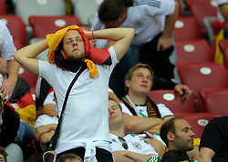 A dejected fan comes to terms with losing their UEFA EURO 2012 semi final match between Germany and Italy at the National Stadium on June 28, 2012 in Warsaw, Poland.