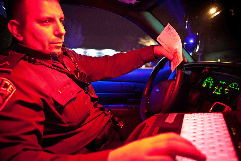 """""""On the job"""" is a tern used by police to describe others involved in law enforcement.    As in """"he's on the job.""""     Here, Arlington Police Officer Constantine Rallis checks his computer after stopping a vehicle belonging to a woman with a suspended license.  The red dome light ensures that the officer does not suffer night blindness.  Photo by Ed Buice"""