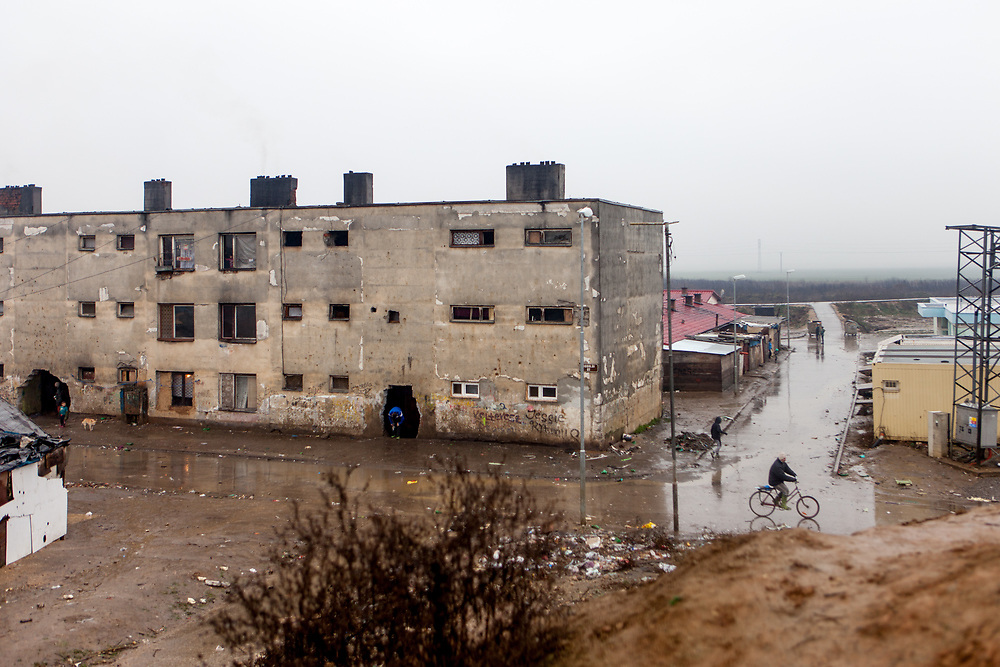 """A decrepit building seen from a little hill at the Roma settlement in Moldava nad Bodvou (2016). In 2015 the """"muddy"""" roads to and in the settlement were asphalted and the infrastructure for the residents  improved. From about 800 inhabitants of the segregated settlement 'Budulovska Street' are roughly 392 children up to the age of 16 years (2014) ."""