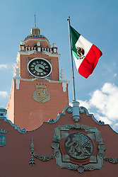 Mexico, Yucatan, Merida, Plaza Mayor (also known as Plaza Grande and Plaza de la Constitucion), clock tower of Palacio Municipal, built in 16th century, and Mexican flag