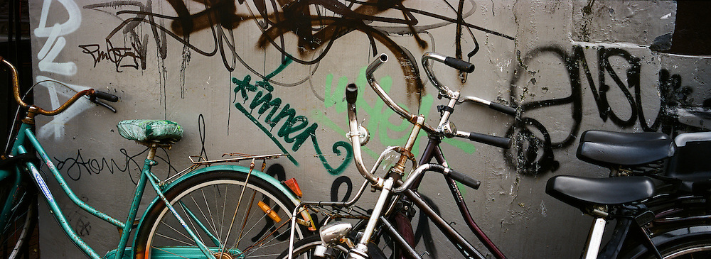 A panoramic view of bicycles parked against a wall covered in graffiti in Amsterdam, Holland. 23rd July 2011. Photo Tim Clayton