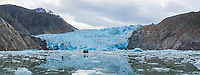 Panorama of a small boat dwarfed by South Sawyer Glacier in Tracy Arm - Fords Terror Wilderness in Southeast Alaska. This tidewater glacier is in rapid retreat due to climate change and provides critical ice for the harbor seals to pup in the spring and early summer.
