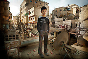 """December 8 , 2012 , Damascus , Syria : Ghadir Daher - 12 - School student , stands on the roof of a house in his neighborhood behind him traces of devastation due to the explosion. On Thursday evening December 6 , 2012 a car exploded in Mazzeh 86 area at al madaress street ( a civilian neighborhood )  leaving behind a number of dead and wounded. Ghadir recounts """"It was a Thursday evening after school. My mom sent me to buy nuts from a shop nearby. Before I arrived there, a car exploded in front of my eyes. My body flew and fell on the ground. In front of me, I saw the body of a woman ripped by the explosion ... awful, awful ?Everyone was screaming. I thought that a second explosion might happen. I got up and ran rapidly toward the house. I found my mother crying and screaming. I told her not to be afraid because I was safe. """" ."""