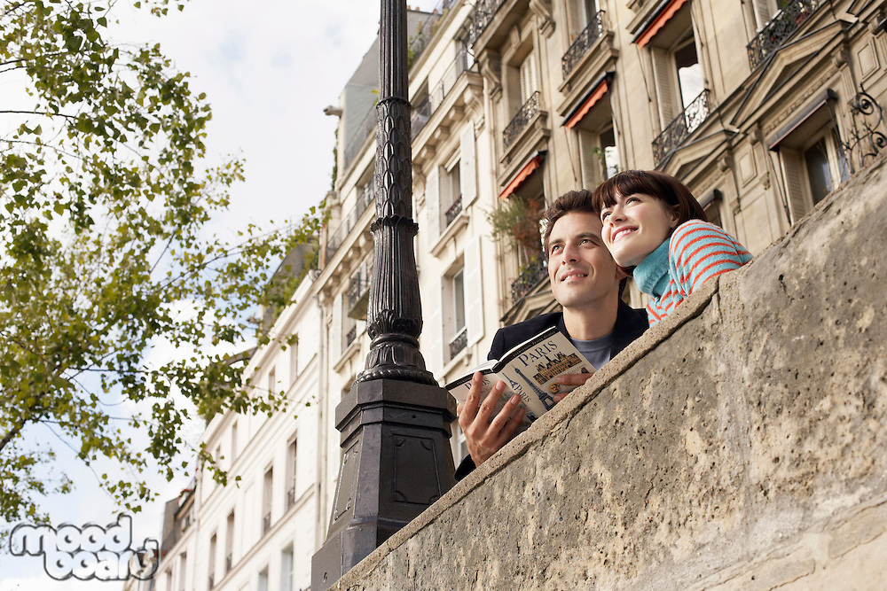 France Paris Couple looking over bridge with guidebook