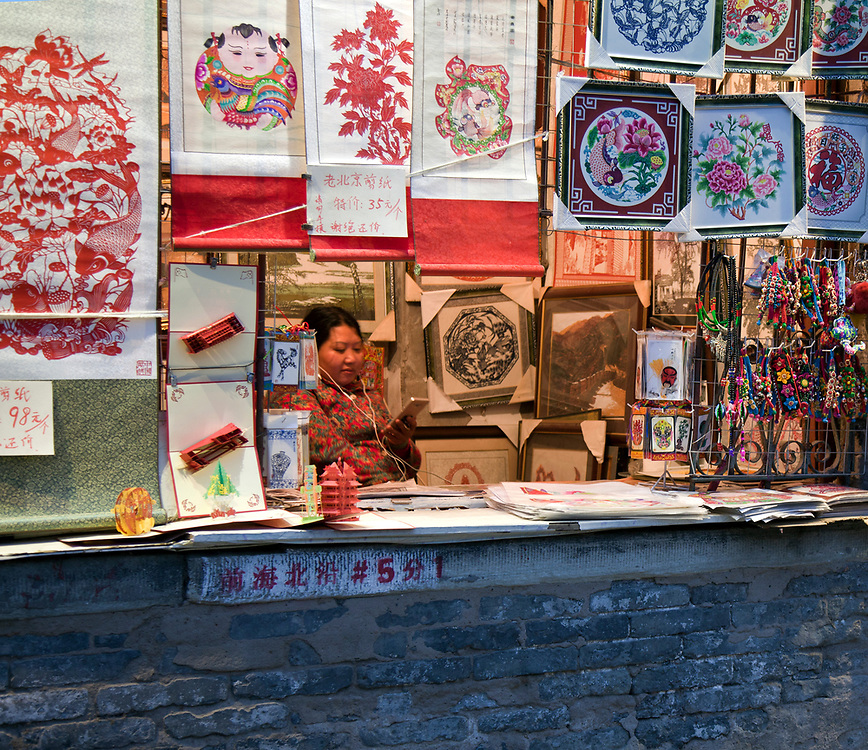 Woman on her cell phone at art souvenir stand, Shichahai (Houhai) Entertainment District at Twilight, Beijing, China.