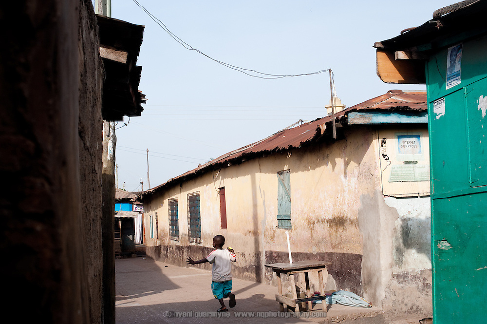 A boy runs down an alley in Nima, a densely populated area of Accra, Ghana.